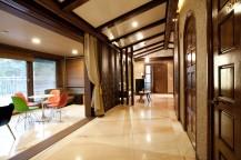 明るく長い廊下が続いており、右手には木製のドア、左手にはいすとテーブルがある。