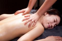 女性が背中のマッサージを受けている。