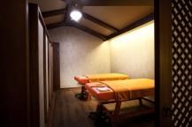ベッドが2台並んでおり、天井には丸い電気がある。