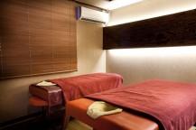 2台のベッドが並んでおり、壁にエアコン、窓にはすだれが垂れ下がっている。