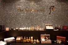 壁にthe history of fの文字が書かれており、下の台には化粧品が並んでいる。