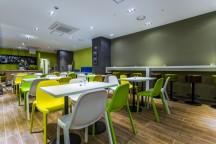 白いテーブルと、黄色、黄緑色、白色のイスが並んでいる。