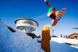 青い空と白い雪があり、奥に展望台があり、手前でスノーボーダーが飛んでいる。