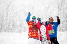 真っ白な雪景色の中で3人の男女が笑顔でこちらに手を振っている。