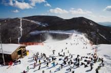スキー場と山と青い空。たくさんのスキーヤーがいる。