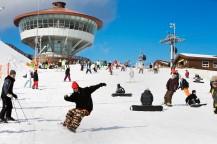 奥に展望台、青い空、白い雪、人々がスノーボードを楽しんでいます。