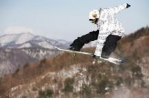 スノーボードを掴んで飛ぶスノーボーダー。