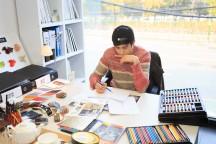 白い机の上に色鉛筆や画用紙が乱雑に置かれており、男性が椅子に座って絵を描いている。