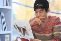鉛筆を持って紙を見ている男性。