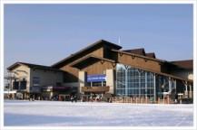 青い空と、雪があり、中央に大きい山小屋がある。