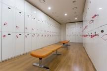 白いロッカーが壁に沿って並んでおり、真ん中にオレンジの長いすが置いてある。