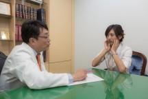 女性と男性が机をはさん向かい合って話をしている。