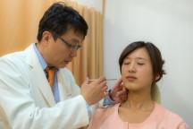 男性が女性の顔に注射を打っている。