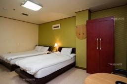 緑の壁の部屋にベッドが2台並んでおり、木のタンスがある。