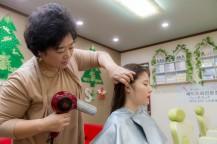 朴先生が女性の髪を乾かしている。