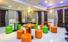丸テーブルのまわりにオレンジと緑の椅子が置いてある。