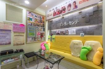 黄色いソファのクッションが置いてあり、壁に芸能人の写真が貼ってある。
