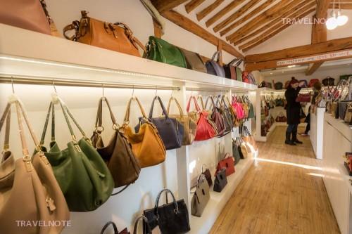 白い壁に沿って色とりどりのバッグがかかっている。