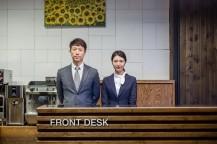 FRONT DESKと書かれた台の後ろに男性1人と女性1人が立っている。
